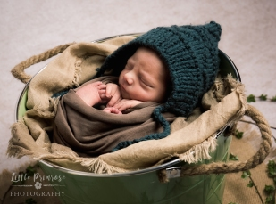 Newborn photography Cheshire - Baby in bucket pose with bonnet
